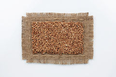 Classical frame made of burlap with grains of buckwheat Royalty Free Stock Photography