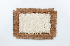 Classical frame made of burlap with grains of rice Royalty Free Stock Image