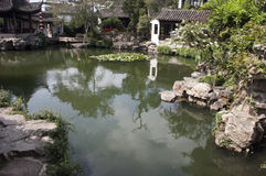 Classical Gardens of Suzhou, China. Designated as a World Heritage site by UNESCO. Water and rocks surround the ancient buildings in a classic Oriental garden royalty free stock image