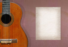 Classical guitar. On grunge wall with blank page of mulberry paper for your note Royalty Free Stock Photo