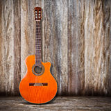 Classical Guitar. A cut away classical guitar on a concrete floor with wood fence background Royalty Free Stock Photo