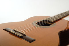 Classical guitar lit from above. Classical Spanish guitar against white background, lit from above, cropped to show only the body and part of the neck Royalty Free Stock Photos