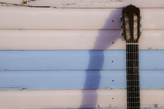 Classical guitar neck against pastel pink and blue beach hut. Classical guitar neck with shadow on the boards of a pastel pink and blue beach hut. Neck to the Stock Photography
