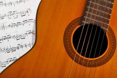 Classical guitar and notes. A classical guitar and a music sheet Stock Image