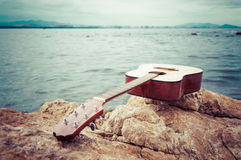 Classical guitar on seaside rock Stock Photo