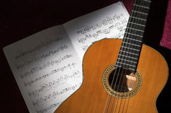 Classical guitar and sheet music in spot light Stock Photography