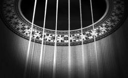 Classical guitar: strings and rosette. Black and white photo. A black and white photo of a part of a classical guitar with the strings and the rosette Stock Image