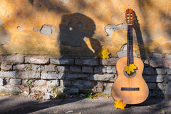 Classical guitar in sunlight next to wall Stock Photo