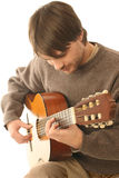 Classical guitarist guitar. Young man playing classic acoustic six string guitar. Guitarist isolated on white background. Details of guitar playing. Focus is on Stock Images