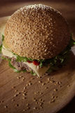 Classical hamburger on a wooden plate. Tasty classical hamburger on a wooden plate Royalty Free Stock Images