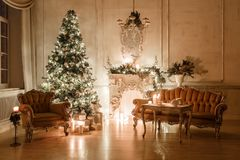 Classical interior of a white room with a decorated fireplace, sofa, Christmas tree, garlands, candles,lanterns, gifts Stock Images