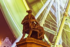 A classical monument of a Greek goddess sitting in front of a ferris wheel moving with a motion blur. Royalty Free Stock Image