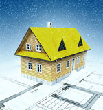 Classical mountain cottage with layout plan and falling snow Royalty Free Stock Photography