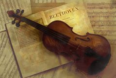 Classical music. Violin lying on top of book about Beethoven and sheets of music stock images
