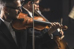 Classical music concert performance. Professional symphonic orchestra performing on stage and playing a classical music concert, violinist playing in the royalty free stock photography