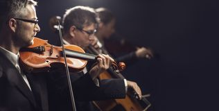 Classical music concert performance. Professional symphonic orchestra performing on stage and playing a classical music concert, violinist playing in the stock photos