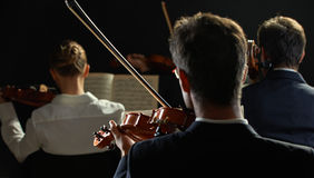 Classical music: concert. Violinists playing at the concert, rear view Royalty Free Stock Photos