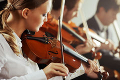Classical music: concert. Violinists playing at the concert, young beautiful women on foreground Royalty Free Stock Images