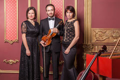 Classical music quartet posing after the concert. Classical music quartet posing after the concert with their instruments in hall and looking at camera. Studio Stock Image