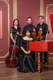 Classical music quartet posing after the concert. Classical music quartet posing after the concert with their instruments in hall and looking at camera. Studio Royalty Free Stock Photography