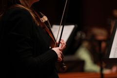 Classical music. Violinists in concert. Stringed, violinist.Closeup of musician playing the violin during a symphony. Classical music. Violinists in concert Royalty Free Stock Image