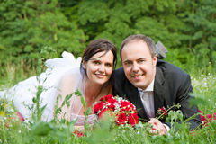 A classical newly wed couple portrait. Classical newly wed couple with wedding gown dark suit and red bridal bouquet the groom and bride lie on a meadow royalty free stock photography