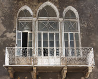 Classical and old architectural detail. Classical architecture in Beirut Lebanon with arched french windows and wrought iron railings framing the verandah Stock Photos