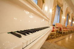 Classical Piano - white and black keys. Golden luxury ballroom Royalty Free Stock Photos