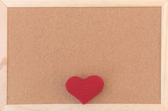 Classical plain brown cork board with red knitting heart at bottom of frame royalty free stock photos