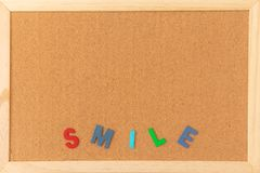 Classical plain brown cork board with wooden colorful SMILE letter at bottom of frame stock image