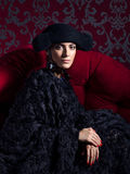 Classical portrait of woman wearing black hat end dress sitting on red sofa. Fashion style Royalty Free Stock Images