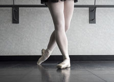 Classical Position of a Ballet dancer. Graceful ballet dancer in classical position preparation in her pointe shoes and practice skirt Stock Image