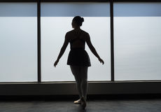 Classical Position ballet dancer silhouette. Ballet dancer in classical position looking outwards in a window frame silhouette Stock Photo