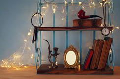 Classical shelf with vintage male objects and blank frame. With gold garland lights. Ready to put photography Stock Photography
