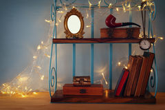 Classical shelf with vintage male objects and blank frame. With gold garland lights. Ready to put photography Stock Images