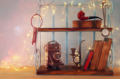 Classical shelf with vintage male objects, decorative old camera. And gold garland lights Stock Photo