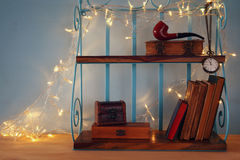Classical shelf with vintage male objects. And gold garland lights Stock Image