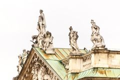 Classical statues on the rooftop of a building. Classical stone carved statues on the rooftop of an old historical building isolated against a white sky stock images