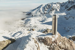 Classical steel thermos in winter in the mountains with mountains in the background Royalty Free Stock Image