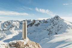 Classical steel thermos in winter in the mountains with mountains in the background Stock Image
