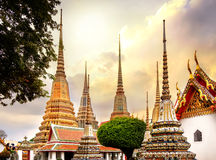 Classical Thai architecture in Wat Pho public temple at dramatic orange sunset sky , Bangkok, Thailand. Wat Pho known also as the Temple of the Reclining Royalty Free Stock Photo