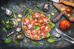 Classical traditional tomatoes mozzarella salad , preparation on dark rustic kitchen table with ingredients , cutting board and cu Stock Photography
