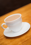 Classical white cup of milk coffee on table blur backgrounds Royalty Free Stock Image