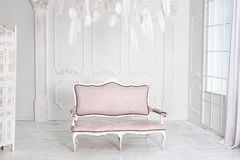 Classical white interior with pink sofa. Stock Photo