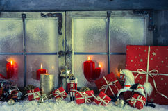 Classical xmas decoration in red and golden colos with a rocking. Classical xmas decoration in red and golden colors: rustic old wooden window with candles for a Royalty Free Stock Photography
