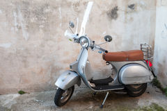 Classical yellow Vespa scooter stands parked Stock Image