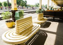 A classically curved design park bench in yellow-cream in the Ayutthaya railway station platform. stock photos