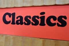 Classics Red Sign Background on a book shelf. Classics Sign Background.The literature of any language in a period notable for the excellence and enduring quality royalty free stock images