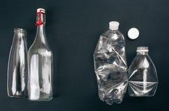 Classificando o desperd?cio Duas garrafas de vidro e plásticas vazias são preparadas reciclando no fundo escuro Reduza reusar rec foto de stock
