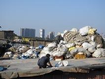 Classificando para fora desperdícios do plástico no precário de Dharavi, Mumbai, Índia Imagens de Stock Royalty Free